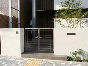 玄関前 壁、門扉の高さを合わせ直線を強調したデザインにする