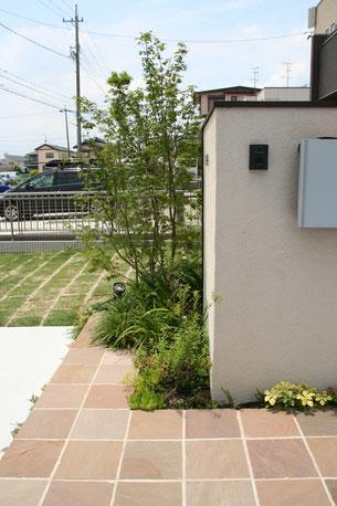 L型の壁の側面にはインターホンとポストを