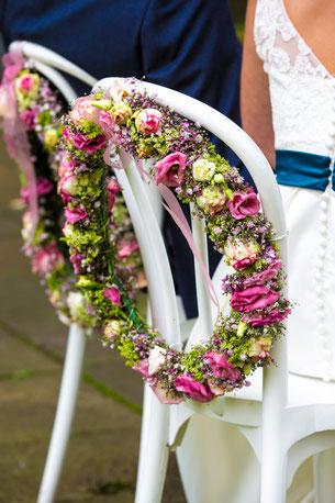 Blütenkränze als Blickfang während die Braut uns bei  der Freien Trauung den Rücken zudreht.