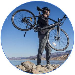 Homme porte son vélo avec un casque