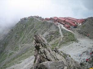 山荘の左、岩の間の緑色(上)が私たちのテントです。
