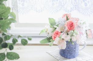 明るい陽射しが差し込む窓辺に置かれた花びん。バラとユリの花。
