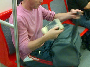Él entra la vagón del metro, encuentra un asiento desocupado y veloz se sienta, abre el bolso y extrae su libro, urgente.
