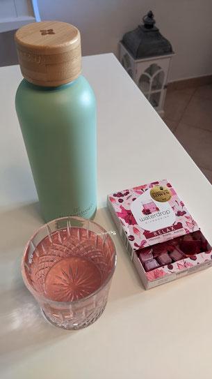 bottiglia in acciaio waterdrop con bicchiere in vetro e microdrink poggiati su un tavolo bianco