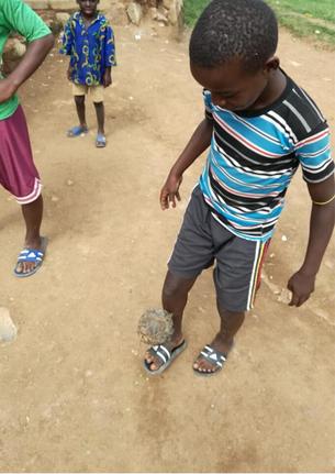 手作りボールでサッカーをする子ども達