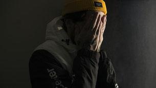 jeune homme qui se cache le visage dans les mains