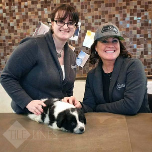 Two Tile Lines employees pose with a black and white puppy on a tile countertop.