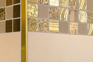 Close up of a corner of two tiled walls. A mixed-texture mosaic of gold square tiles against a cream-colored field tile, with a brushed brass Schluter Jolly trim.