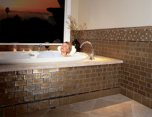 Woman enjoying a bubble bath in a soaking tub framed with iridescent gold glass tiles.