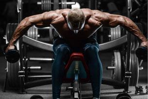 Ein athletisch gebauter Mann sitzt auf einer Bank und mit Gewichten für Schulter-Übung