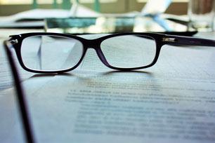 Paire de lunettes posées sur un contrat