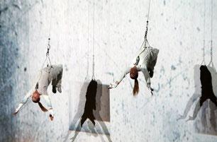 Zwei Frauen hängen an Kletterseilen an der Wand, weiß gekleidet, tanzen an der Wand. Tanz an der Wand Vorarlberg