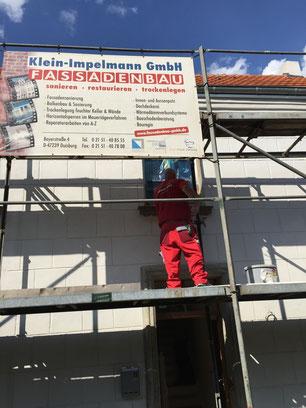 Fassadenrestaurierung in Duisburg-Baerl - Gerüst mit Fassadenbau-Baustellenschild. Nach erfolgreicher mechanischer Trockenlegung im Mauersägeverfahren erfolgt nun die Restaurierung der Fassaden mit denkmalgerechten Sanierungsmörteln der Firma  TUBAG. Als