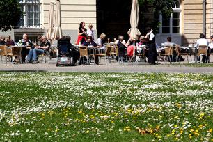 Menschen sitzen im Cafe im Theaterbau des Schloss Charlottenburg im Freien. Foto: Helga Karl