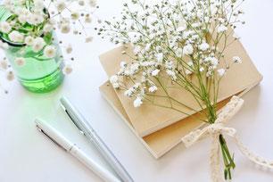 カスミソウのブーケ。ノートとボールペン。ガラスのコップにもカスミソウが活けられている。