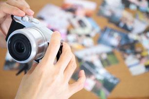 テーブルの上のノートパソコン、スマホ、ノート、ペン、花びん。