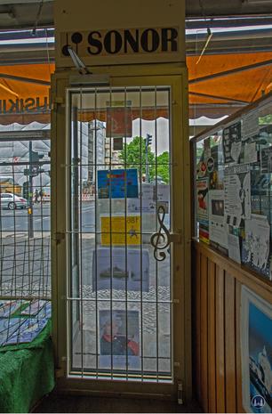 Musikhaus Bading in Berlin - Neukölln, Karl - Marx - Straße. Ladentür mit Griff in Form eines Notenschlüssels.