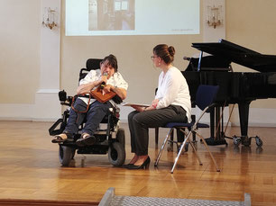 Das Foto zeigt 2 Frauen auf der Bühne, die sich unterhalten. Die eine Frau sitzt in einem Rollstuhl.