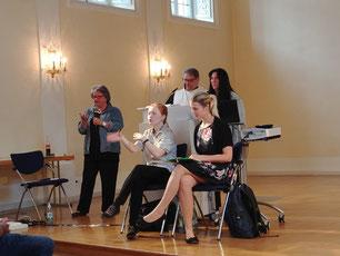 Das Foto zeigt 2 Frauen und einen Mann am Rednerpult. Davor sitzen 2 Gebärdensprachdolmetscherinnen.