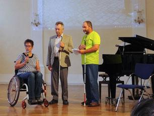 Das Foto zeigt auf der Bühne 3 Personen. Eine Frau im  Rollstuhl und zwei Männer mit Langstöcken.