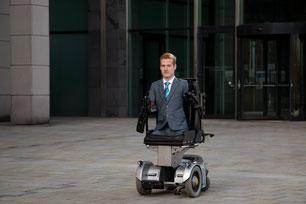 Bürogebäude aus Glas mit einer Drehtür im Hintergrund. Davor Janis McDavid ohne Arme und Beine in seinem Rollstuhl sitzend.