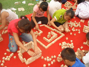 """Just like in Japan, they build """"squares of wood blocks (TSUMIKI)"""" on the red carpet. When it is fine weather, we conduct the play outdoors so that the children can freely enjoy."""