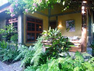 Veranda des 2-Zimmer-Bungalows, mit Ylang Ylang am Eingang, mit Bougenville umrankt, Bambussofa und Bambussessel