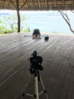 yoga teacher shooting a video in outdoor yoga shala with sea view in Nicaragua