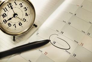 Kalender, Stift und ein Wecker