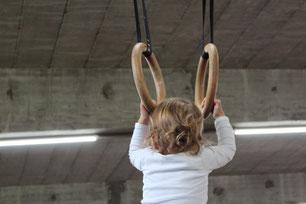 Kleines Kind an den Ringen im Turnsaal