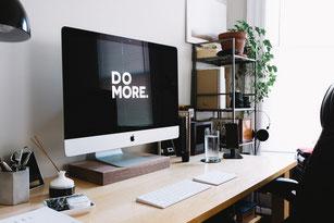 "Ecran posé sur un bureau, où est inscrit ""faire plus"""