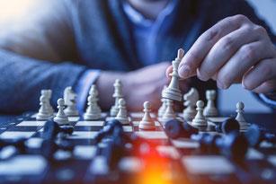 Gros plan sur un jeu d'échecs et en arrière-plan le joueur réfléchissant à sa stratégie