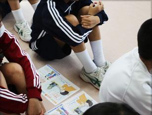 当会作成のチラシを横において、体育会で体育座りして、盲導犬の啓発についての話を聞いている中学生たち。