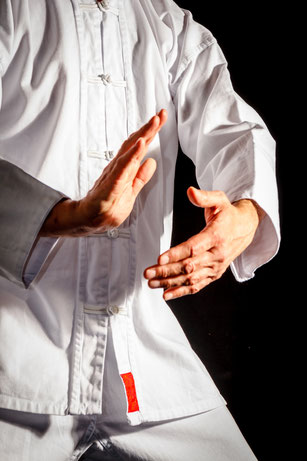Eine Person trainiert Tai Chi in weißer chinesischer Kleidung. Man sieht seine Körpermitte und seine beiden Hände.