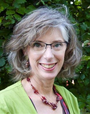 vriendlijk lachhende vrouw, Joke Zonneveld, met groen vest, lichtkrullend, en grijzend haar, met bril, groene ogen, voor beukenhaag