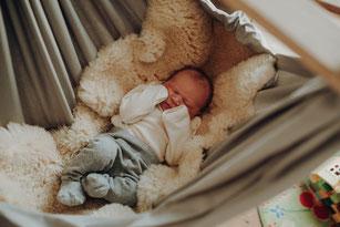 schlafendes Baby hält einen Finger einer erwachsenen Hand