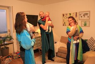 drei Personen mit jeweils einem Baby im Arm binden Tragetücher bei einer Trageberatung