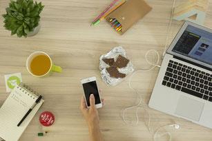 Hand hält ein Handy, heraum sind Laptop, Tasse, Stift und Schreibblock, Schokolade und Tee