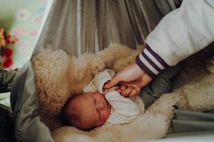 lachendes Baby in einer Babyhängematte liegt auf einem Schaffell