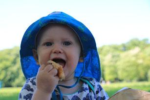 Babyhände halten eine Avocado
