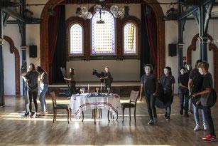 Inszenierung: Rund um einen gedeckten Shabbat-Tisch in Rehburgs historischem Bürgersaal tragen die Jugendlichen die Juden Rehburgs zur Tür hinaus.