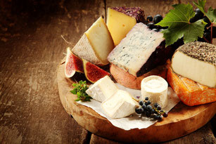 Mediterranean cheese selection on wooden board.