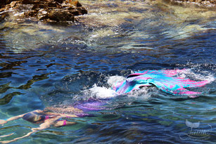 Jamie Jaime the Mermaid swimming in a rock pool, Eden, New South Wales, Australia. Blonde underwater mermaid. Pink, purple, blue aqua mermaid tail.