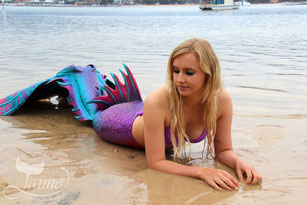 Jamie Jaime the Mermaid swimming at Mitchies Jetty, Merimbula, New South Wales, Australia. Blonde underwater mermaid. Pink, purple, blue aqua mermaid tail.