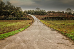 Einsamer Weg zwischen Feldern und Äckern