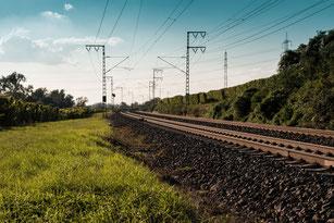 Schienen-Gleise mit Schotter und Oberleitungen
