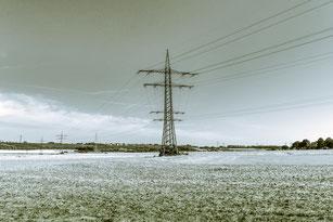 Strommasten im Feld bei gefrorenenem Boden