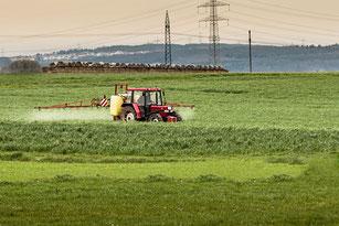 Feldspritze in Aktion auf Acker