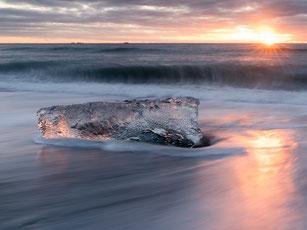 Klares Gletschereis am Strand in Island. Im Hintergrund ein wunderbarer Sonnenuntergang.