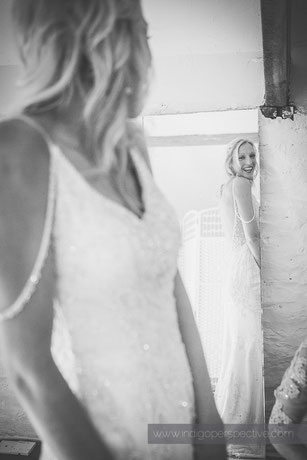bride looks in mirror at wedding dress smiling. westcott barton north devon wedding photography